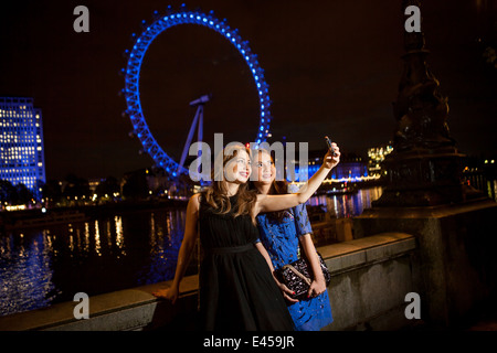 Two young female friends taking self portrait at night, London, UK - Stock Photo