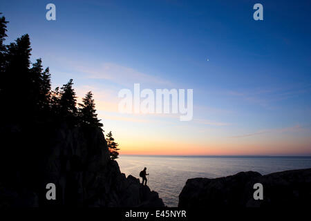 Lone hiker at sunrise on the Bold Coast trail in Cutler, Maine, USA, June 2009. Model released. - Stock Photo