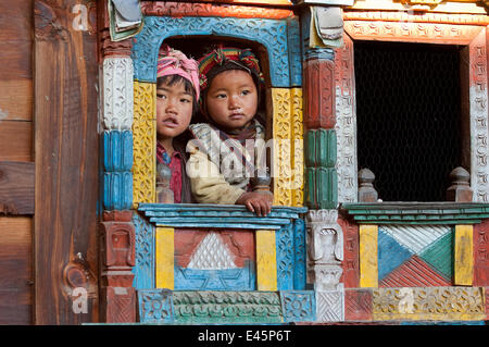 Two children looking through decorated window of traditional building. Tamang ethnic group,  Gadlang, Langtang region, - Stock Photo