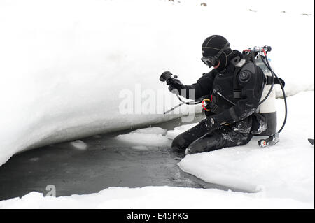 Doug Allan, BBC cameraman, preparing to enter ice-hole for underwater filming, McMurdo Sound, Ross Sea, Antarctica, - Stock Photo