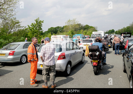 Motorbikes driving riding through stationary vehicles in a traffic jam with people standing on carriageway on M6 - Stock Photo