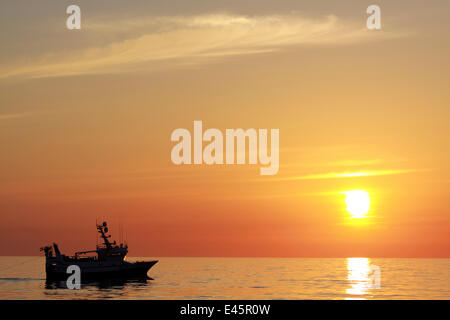 Trawling on the North Sea in calm conditions at sunset, May 2010. Property released. - Stock Photo