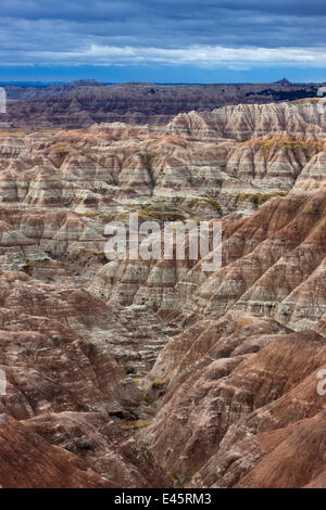 View of Badlands National Park, with shadows cast between mountain peaks, and sediment layers visible, South Dakota, - Stock Photo
