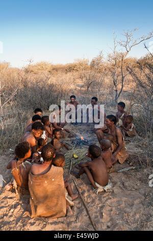 Kalahari bushmen, family sitting round fire in the bush, dry season, Central Kalahari Desert, Botswana, August 2008 - Stock Photo