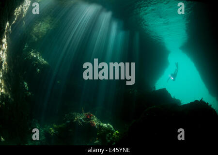 Light streaming into a shallow cave in dive site called The Passage, with a snorkeler swimming down into the entrance. - Stock Photo