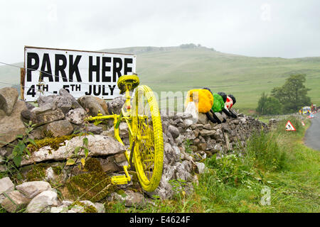 Kilnsey en-route to Kettlewell,  Yorkshire Dales, UK 3rd July, 2014.  Cycle imbedded in stone wall a decorations - Stock Photo