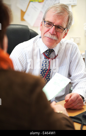 Male GP in small NHS surgery is in a consultation with a patient - Stock Photo