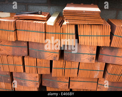 self building house, bundles of traditional clay rosemary roofing tiles - Stock Photo