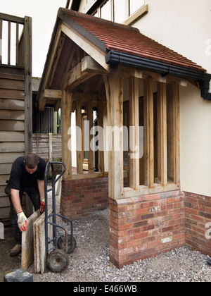 self building house, man laying natural Indian stone paving around brick and green oak porch onto prepared base - Stock Photo