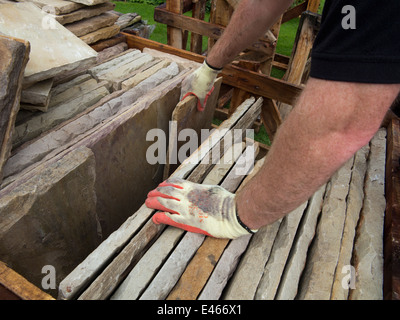 self building house, builder sorting natural Indian stone slabs - Stock Photo