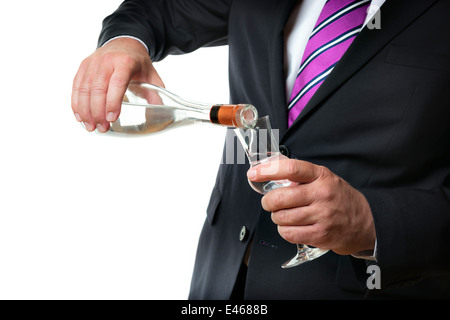 Business man in dark suite with a grappa glas and a bottle with alcohol - Stock Photo