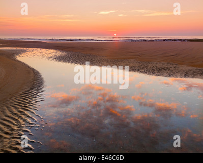 Ocracoke Island, North Carolina: Sunrise clouds reflected in a tide current on a quiet beach - Cape Hatteras National - Stock Photo