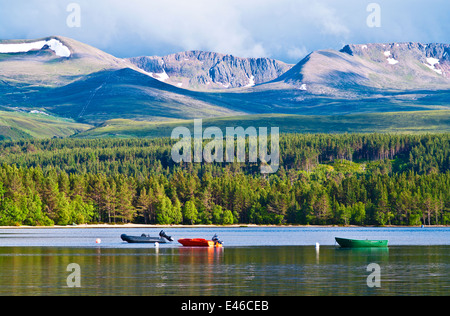 Coire an t-Sneachda rises above Glenmore Forest and boats moored on Loch Morlich, the Cairngorms near Aviemore, - Stock Photo