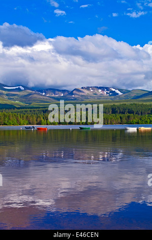 The Northern Corries and Glenmore forest seen across loch Morlich, boats moored, calm summer evening, near Aviemore, - Stock Photo