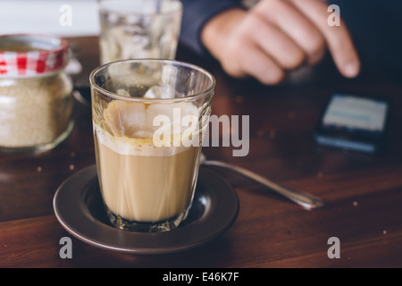 a man using his phone whilst in a cafe - Stock Photo