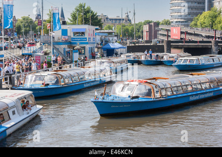Amsterdam Central Station Cruise boats lining up to take tourists on a canal tour through famous canals of the Grachtengordel. - Stock Photo