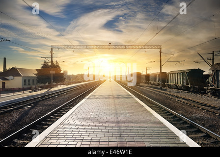 Boxcar on the station at sunset with clouds - Stock Photo
