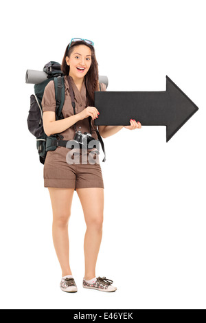 Full length portrait of a female tourist holding a black arrow pointing right - Stock Photo