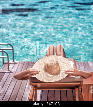 Young woman sitting on wooden pier on the sea wearing hat and taking sun bath, enjoying perfect summer day, - Stock Photo