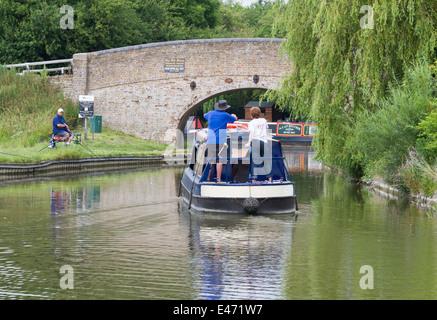 A narrowboat approaching Bridge 126 at Pitstone Wharf, Buckinghamshire, England on 23 June 2014. - Stock Photo