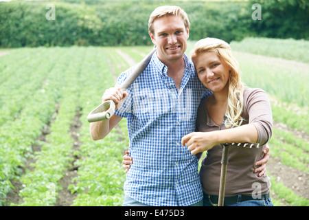 Couple Working In Field On Organic Farm - Stock Photo
