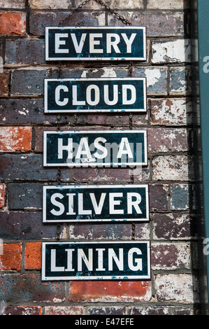 Signs on a brick wall saying 'Every cloud has a silver lining' - Stock Photo