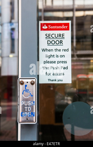 Button on a Santander Bank door advising customers to push the button for access. - Stock Photo