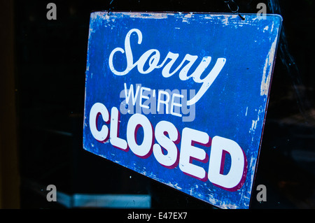 Sign on a shop saying 'Sorry. We're closed' - Stock Photo