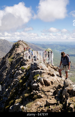 View along Crib Goch ridge top scramble with hikers scrambling at start of Snowdon Horseshoe in mountains of Snowdonia - Stock Photo
