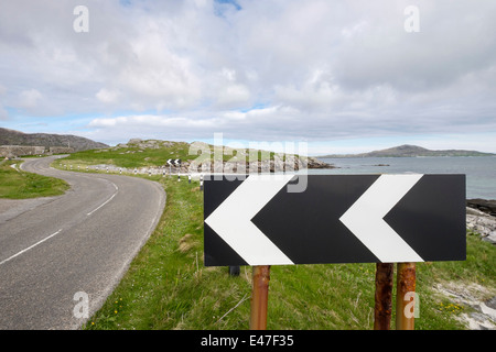 Black and white chevron sign warning sharp lefthand bend on a coast road on South Uist Outer Hebrides Western Isles - Stock Photo