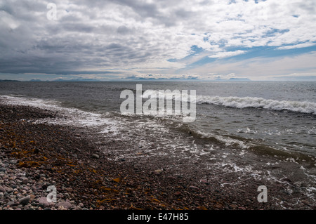 Looking at the Isle of Skye from Melvaig shore on a cloudy day across The Minch - Stock Photo