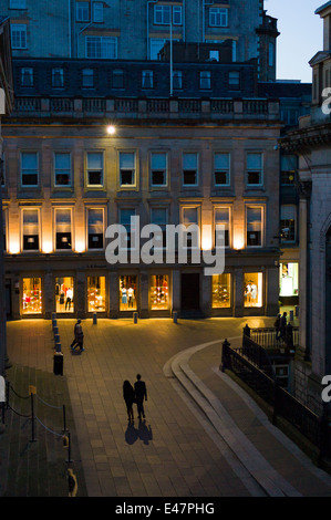 Couple holding hands and taking a nighttime stroll in Royal Exchange Square in the City Centre, Glasgow. SCOTLAND - Stock Photo