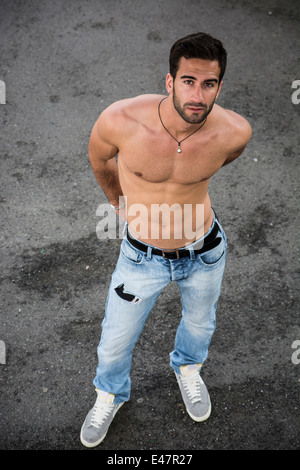 Handsome bearded shirtless young man standing on asphalt ground, looking at camera, shot from above - Stock Photo
