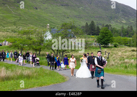 Highland Scottish wedding.  Piper leads procession of bride, groom and guests from Clachan Church in the Highlands - Stock Photo