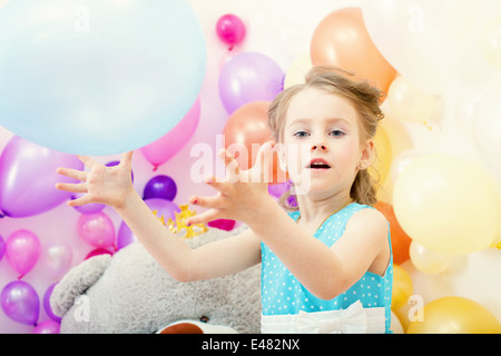 Funny little girl plays with balloon in studio - Stock Photo