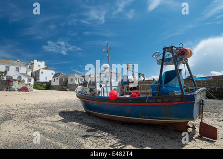 A fishing boats stranded on the sandy beach in St Ives Cornwall while the tide is out - Stock Photo