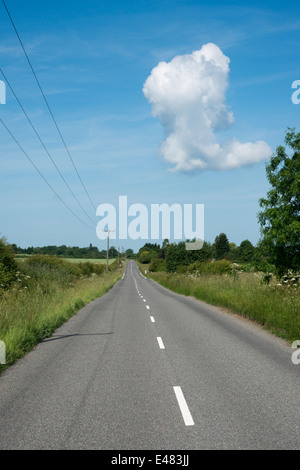 A straight country road in the UK, empty, leading to a vanishing point with blue sky and one white cloud - Stock Photo
