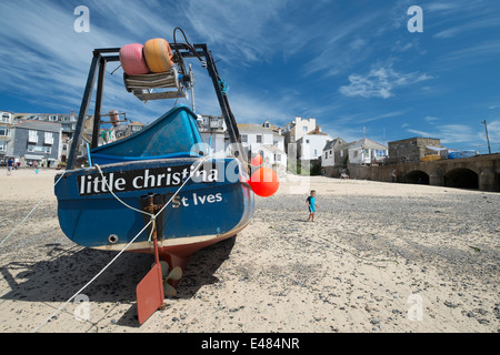 A young child walking on the beach at St Ives in Cornwall next to the fishing boat little christina - Stock Photo