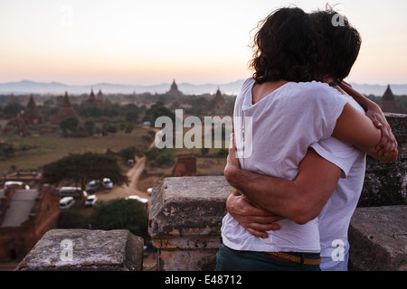 A young couple embracing and enjoying sunset on top of Shwesandaw temple in Bagan, Myanmar (Burma) - Stock Photo