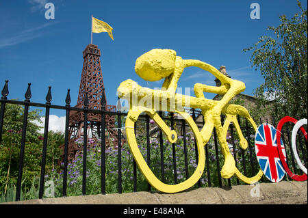 Under blue sky, wooden Eiffel Tower with flag & close-up of yellow model of cyclist fixed to garden fence, built - Stock Photo