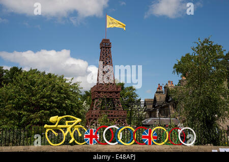 Under blue sky, wooden Eiffel Tower with flag & yellow model of cyclist fixed to garden fence, built to celebrate - Stock Photo