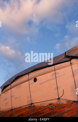 Boat out of water. In the process of being repainted. - Stock Photo