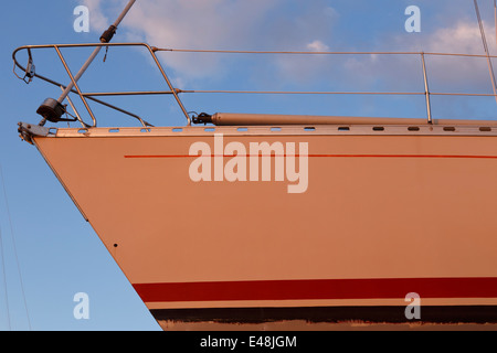 Yacht out of water, just been repainted orange. - Stock Photo