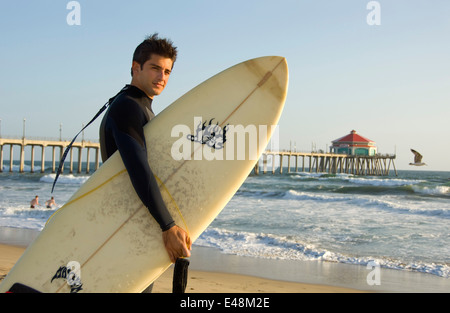 Surfer at Huntington Beach Pier in Orange County, CA - Stock Photo