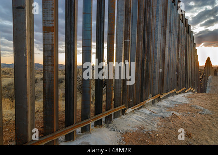 Sunset at US Border Fence, east of Nogales Arizona USA, viewed from US side, looking west toward Nogales, Arizona - Stock Photo