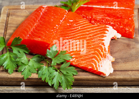 fresh red salmon fillets on traditional wooden server - Stock Photo