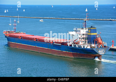 'Behcet C' bulk carrier departs Port Ravenna along Candiano Canal heading out into the Adriatic sailing boats beyond - Stock Photo