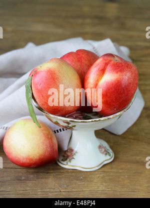 ripe fresh pink peaches in vase on a wooden table - Stock Photo