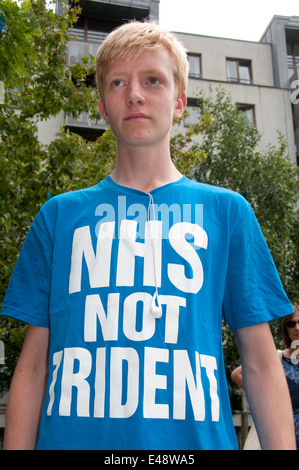 Rally against proposed cuts to National Health Service doctors' surgeries. A young man wears a t shirt saying 'NHS - Stock Photo