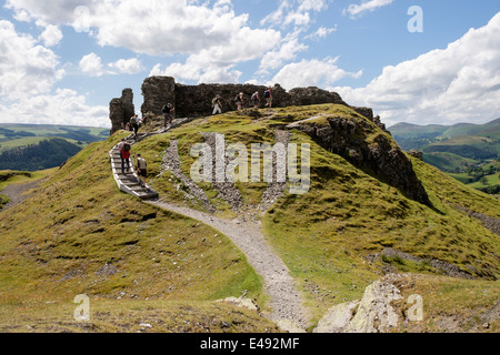 Walkers on path to 13th century Castell Dinas Bran castle remains on Iron Age hilltop fort site Llangollen Denbighshire - Stock Photo